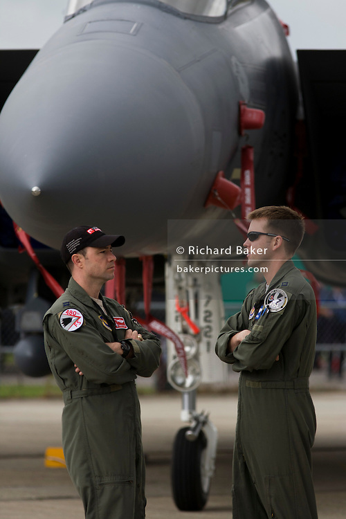 Two US Air Force crew stand below the nose of their F-16C fighter jet at the Farnborough Air Show, UK.