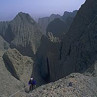 Sam Lightner (MR) rappels off Shipton's Arch, above arid slot canyons in the Kara Tagh Mountains near Taklimakan Desert.