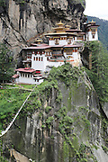 The Tiger's Nest Buddhist temple perched high up, and almost inaccessible except for a steep 3 hour climb, Paro, Bhutan..Bhutan the country that prides itself on the development of 'Gross National Happiness' rather than GNP. This attitude pervades education, government, proclamations by royalty and politicians alike, and in the daily life of Bhutanese people. Strong adherence and respect for a royal family and Buddhism, mean the people generally follow what they are told and taught. There are of course contradictions between the modern and tradional world more often seen in urban rather than rural contexts. Phallic images of huge penises adorn the traditional homes, surrounded by animal spirits; Gross National Penis. Slow development, and fending off the modern world, television only introduced ten years ago, the lack of intrusive tourism, as tourists need to pay a daily minimum entry of $250, ecotourism for the rich, leaves a relatively unworldly populace, but with very high literacy, good health service and payments to peasants to not kill wild animals, or misuse forest, enables sustainable development and protects the country's natural heritage. Whilst various hydro-electric schemes, cash crops including apples, pull in import revenue, and Bhutan is helped with aid from the international community. Its population is only a meagre 700,000. Indian and Nepalese workers carry out the menial road and construction work.