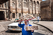Cairo, Egypt, 2 aug 2012, Woman carrying flatbread on the street of Cairo