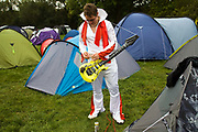 A man dressed as Elvis Presley attempts to fasten his inflatable guitar with string outside his tent at the Standon Calling Festival in Hertfordshire, UK<br /> Standon Calling is a small independent festival set among the hills in Herfordshire that showcases World Music, Indie Music and dance Music. It is one of the new, small and quirky boutique festivals which have become popular in the UK.