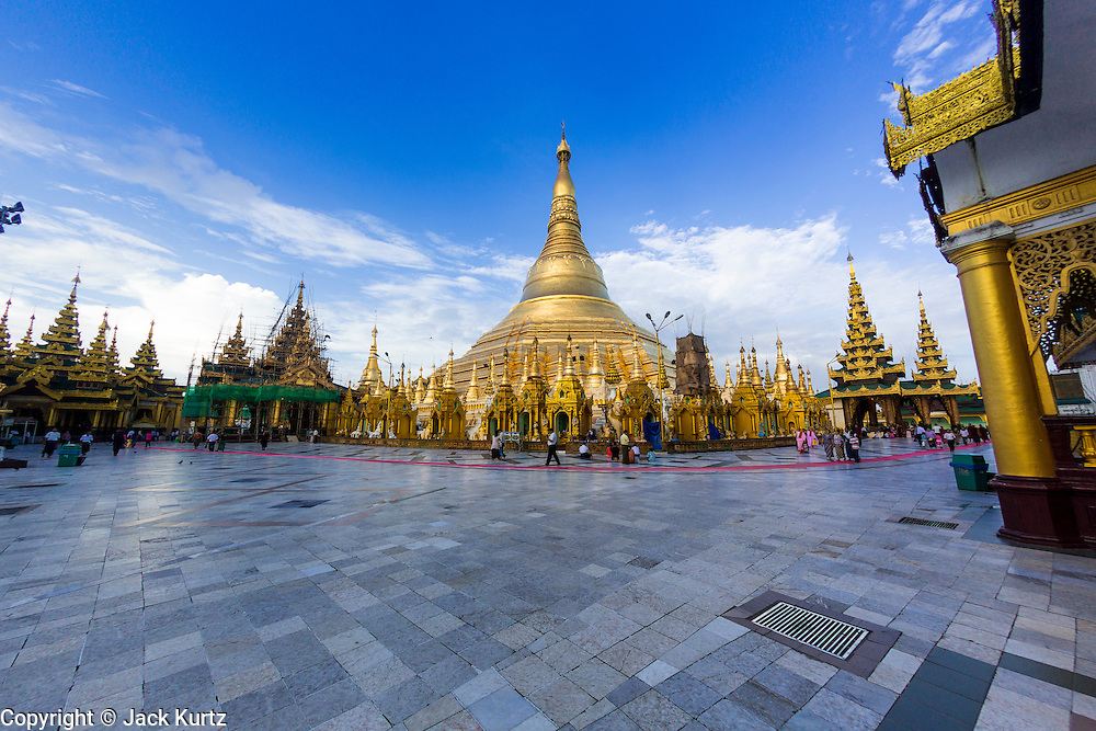 15 JUNE 2013 - YANGON, MYANMAR:  People walk around Shwedagon Pagoda in Yangon. Shwedagon Pagoda is officially known as Shwedagon Zedi Daw and is also called the Great Dagon Pagoda or the Golden Pagoda. It is a 99 metres (325ft) tall pagoda and stupa located in Yangon, Burma. The pagoda lies to the west of on Singuttara Hill, and dominates the skyline of the city. It is the most sacred Buddhist pagoda in Myanmar and contains relics of the past four Buddhas enshrined: the staff of Kakusandha, the water filter of Koṇāgamana, a piece of the robe of Kassapa and eight strands of hair fromGautama, the historical Buddha. The pagoda was built between the 6th and 10th centuries by the Mon people, who used to dominate the area around what is now Yangon (Rangoon). The pagoda has been renovated numerous times through the centuries. Millions of Burmese and tens of thousands of tourists visit the pagoda every year, which is the most visited site in Yangon.  PHOTO BY JACK KURTZ