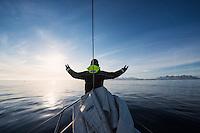 Sailor raises hands towards sun as land approaches off east coast of Greenland