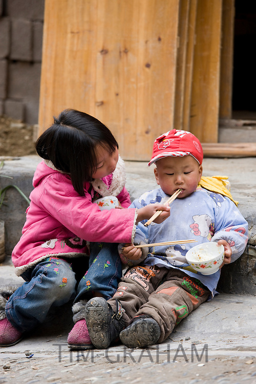 Young girl being sisterly with boy as they eat rice, in Ping An. China has a one child policy to limit population.