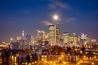 The setting moon over the Calgary city skyline just before sunrise on March 23, 2016.<br /> <br /> ©2016, Sean Phillips<br /> http://www.RiverwoodPhotography.com