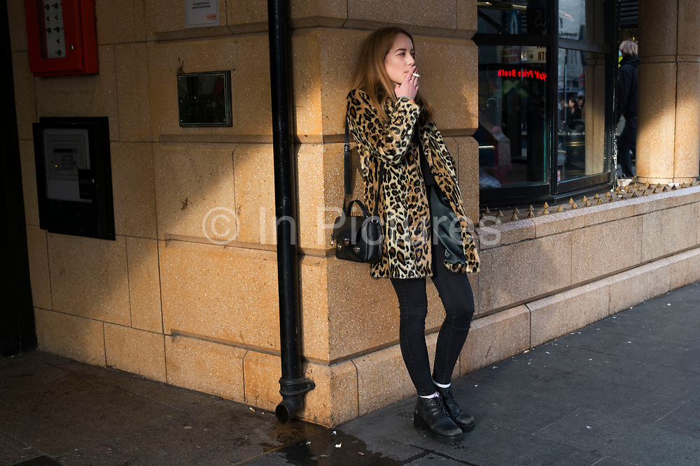 Girl wearing a leopard print fur coat smoking a cigarette while she waits in Leicester Square in London, England, United Kingdom. Her stytlish look blending in with the colour of her surroundings almost camouflage in the evening light. (photo by Mike Kemp/In Pictures via Getty Images)