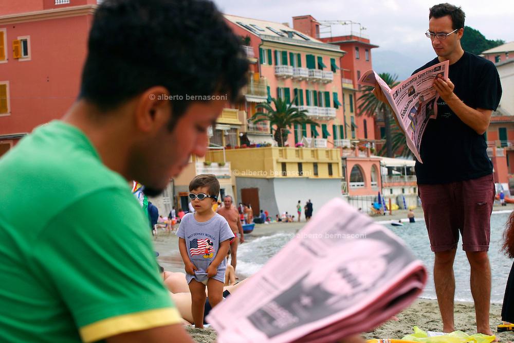 """ITALY, Liguria, Sestri Levante: lettura della gazzetta nella Baia del Silenzio.....ITALY, Liguria, Sestri Levante: reading sport newspaper in the beach of """"Baia del Silenzio""""."""