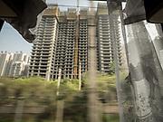 Buildings under construction in the suburbs of Xian. Life in the train from Hong Kong to Urumqi (Xinjiang).