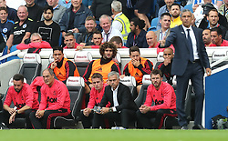 Manchester United's Chris Smalling (top row), Fellaini, Ander Herrera and Lee Grant alongside coach Kieran McKenna (bottom centre), manager Jose Mourinho and coach Michael Carrickon on the bench during the Premier League match at the AMEX Stadium, Brighton.
