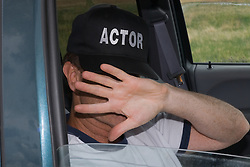 Man sitting in a car wearing an Actor's cap hiding his face with his hand
