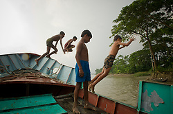 """children   from the fishing village of South Tetulbarian in Barguna Sadar upazila  in Bangladesh play on a boat October 20, 2010 . Because of climate change, the seas are getting more violent, less predictable and boats are capsizing more frequently. Twenty percent of the women in this village are widows because so many have lost their husbands in the seas. Coastal and fishing populations are particularly vulnerable and Fishing communities in Bangladesh are subject not only to sea-level rise, but also flooding and increased typhoons. Erosion as a result of stronger and higher tides, cyclones and storm surges is eating away Bangladesh's southern coast.  Yet the largely fishing community cannot live without the sea. """"We only know how to catch fish,"""" say the fishermen. ( Ami Vitale)"""