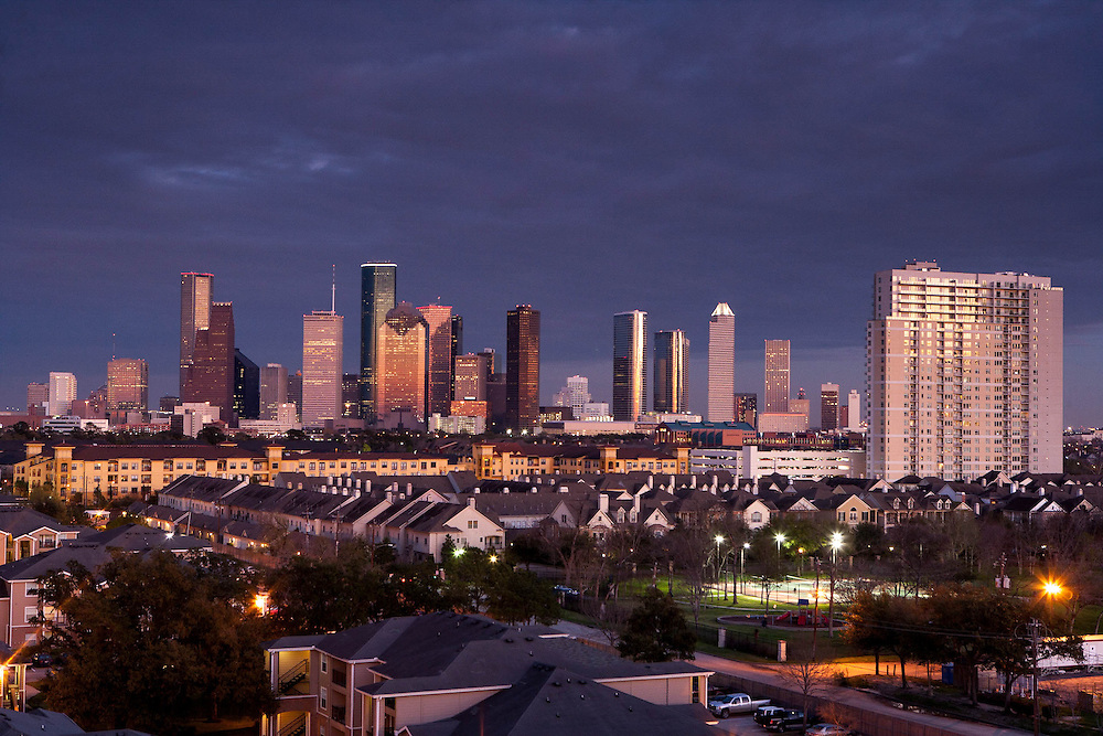 Western view of the Houston, Texas skyline with residential neighborhood in the foreground at dusk.