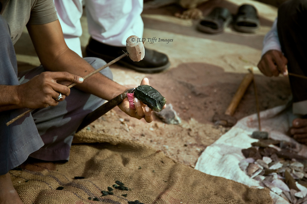 Flaking stone knives using inverse indirect percussion technique with wooden hammer against an iron spike embedded in the ground.