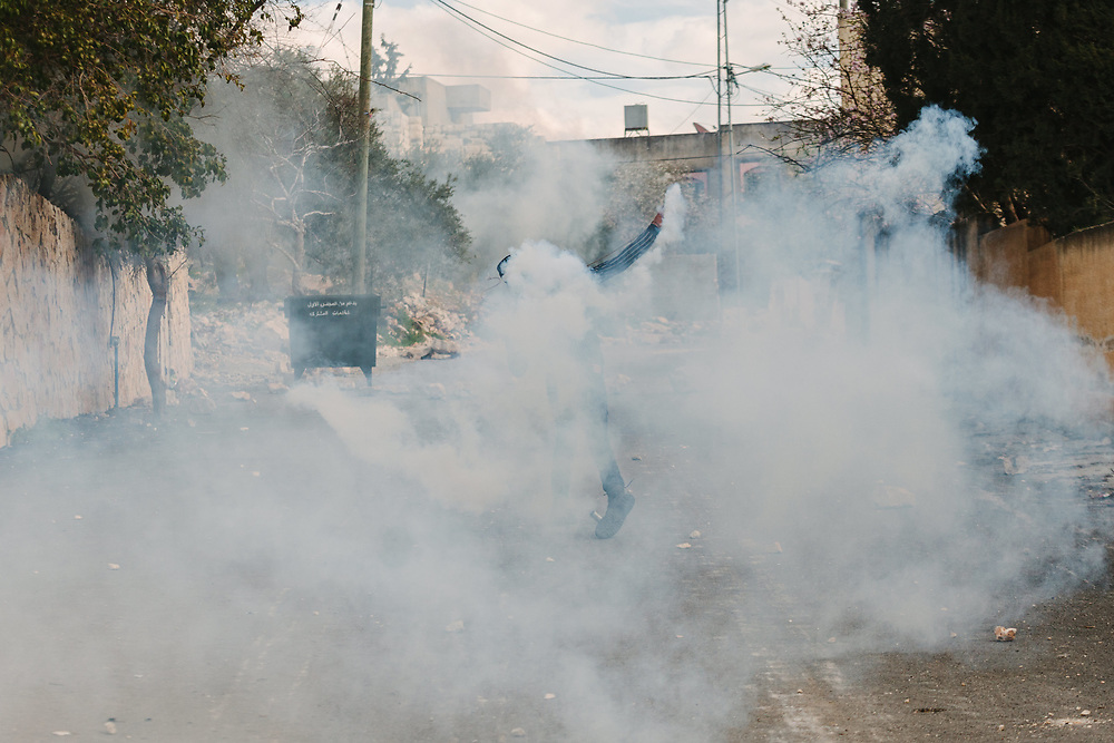 A Palestinian man shrouded by a cloud of tear gas fired by Israeli forces throws away a tear gas canister, during a weekly demonstration against the expropriation of Palestinian land by Israel and against the closure of the main road leading to Nablus, in the Palestinian village of Kufr Qaddum, West Bank, on February 21, 2020.