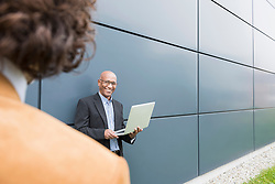 Two businessmen African Caucasian talking laptop
