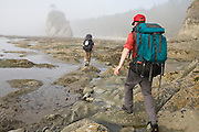 Backpackers navigate the rugged coastline at Norwegian Memorial, North Coast, Olympic National Park, Washington.