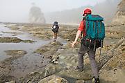 Backpackers navigate the rugged coastline at Norwegian Memorial, North Coast, Olympic National Park, Washington.