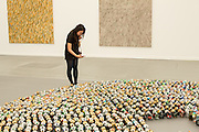 """A woman takes a photograph of an installation of thousands of beer cans entitled """"Halam Tawaal"""", by Kader Atlia, in the Lehmann Maupin booth."""