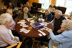Group of elderly people enjoying a card game at a day centre,