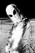 Model wearing silver and alien mask in desert