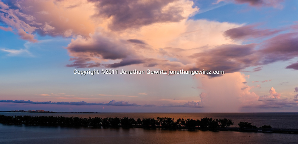 Panoramic view of a late-afternoon rain shower over the Atlantic Ocean near the mouth of Biscayne Bay, with the Rickenbacker Causeway in the foreground. The southern tip of Key Biscayne appears in the left background and the Turkey Point nuclear power plant appears in the right background. WATERMARKS WILL NOT APPEAR ON PRINTS OR LICENSED IMAGES.