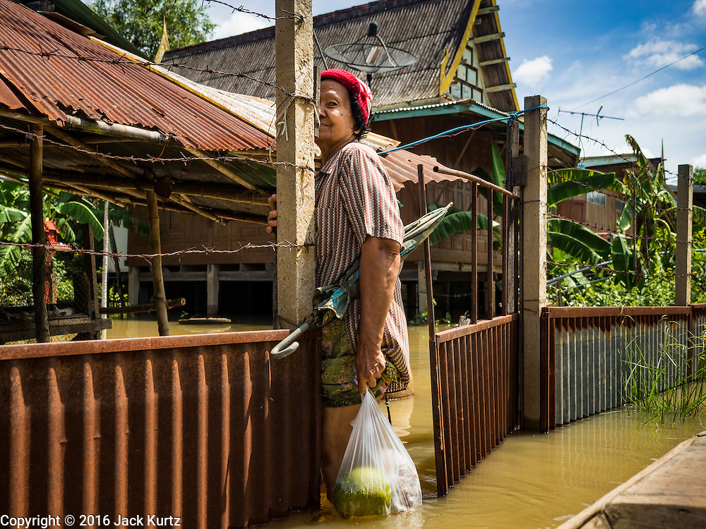 30 SEPTEMBER 2016 - SAI NOI, AYUTTHAYA, THAILAND:  A woman goes into her flooded home in Sai Noi. The Chao Phraya River, the largest river that runs through central Thailand, has hit flood stage in several areas in Ayutthaya and Ang Thong provinces. Villages along the river are flooded and farms are losing their crops due to the flood. This is the same area that was devastated by floods in 2011, but the floods this year are not expected to be as severe. The floods are being fed by water released from upstream dams. The water is being released to make room for heavy rains expected in October.     PHOTO BY JACK KURTZ