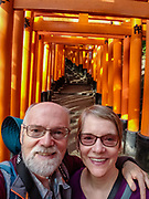 """Tourists posing. Fushimi Inari Shrine (Fushimi Inari Taisha) is an important Shinto shrine in southern Kyoto, Japan. Bright vermilion Senbon Torii (""""thousands of torii gates"""") straddle a network of trails behind its main buildings. The trails lead into the wooded forest of the sacred Mount Inari (233 meters). Fushimi Inari is the most important of several thousands of shrines dedicated to Inari, the Shinto god of rice. Foxes are thought to be Inari's messengers, honored in many statues. The shrine predates the capital's move to Kyoto in 794. The torii gates are donated by individuals and companies, as inscribed on the back of each gate. Prices for small to large gates run from 400,000 to over one million yen. To license this Copyright photo, please inquire at PhotoSeek.com."""