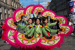 Edinburgh, Scotland, UK. 15 August 2019. Warm sunny weather in Edinburgh brought thousands of tourists onto the Royal Mile to enjoy the many street performers and actors promoting their shows during the Edinburgh Festival Fringe. Pictured cast from the Merry Wives of Seoul.  Iain Masterton/Alamy Live News ++ Editorial Use Only ++
