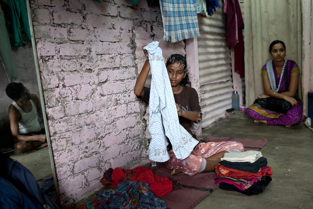 Mayuri Mahesh Pandit, 13, (centre) is tidying up some clothes inside her house, before leaving to participate at the Unicef-run 'Deepshikha Prerika' project inside the Milind Nagar Pipeline Area, an urban slum on the outskirts of Mumbai, Maharashtra, India, where she resides with her family. Her eldest sister, Minal, 20, (right) came to visit her family, while their father Mahesh Kashinath Pandit, 42, (left) is talking to her.