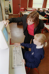 Female secondary school teacher helping student use computer in classroom,