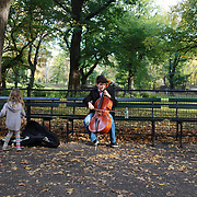 NEW YORK, NEW YORK - NOVEMBER 4: A three year old girl gives money to a young busker in a fall scene in Central Park, Manhattan, New York.  4th November 2017. (Photo by Tim Clayton/Corbis via Getty Images)