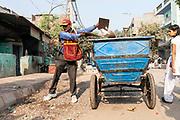 Pradip Kumar, 38, a formal sanitation worker, cleans the street in the Govindpuri slum, New Delhi, India