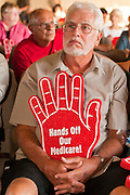 16 MAY 2011 - PHOENIX, AZ: WAYNE LEITZ, from Phoenix, AZ, holds up a foam hand supporting Medicare at a town hall meeting in Phoenix Monday. About 200 people attended Congressman Ben Quayle's (R-AZ) town hall meeting in the Anthem neighborhood of Phoenix, AZ, Monday. Quayle, son of former Vice President Dan Quayle, was elected in the Republican tide that captured the House of Representatives in Nov. 2010. Quayle tried to run under a Tea Party banner. Most of the people in the crowd were hostile to Quayle and the GOP budget proposal that would change medicare to a voucher system and Quayle was shouted down several times when he tried to support the budget.     Photo by Jack Kurtz / ZUMA Press