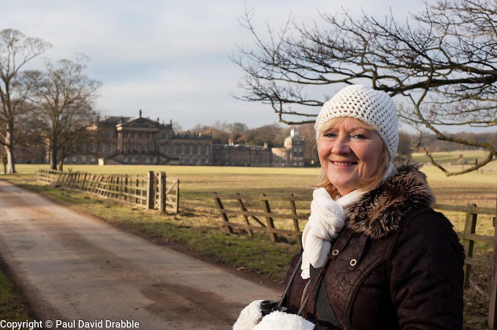 Aileen stood in front of Wentworth Woodhouse, a Grade I listed country house near the village of Wentworth in South Yorkshire. The East Front is  606 ft (185 m) long and is the longest country house façade in Europe..The house includes 365 rooms and covers an area of over 2.5 acres (10,000 Sq meters)..29 January 2010.Images © Paul David Drabble