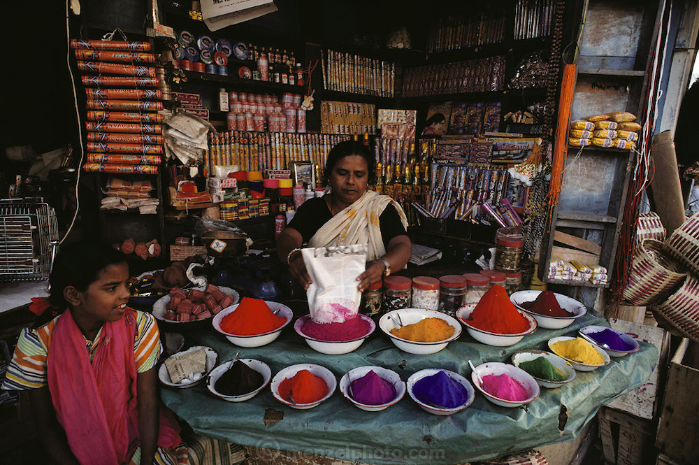 A rainbow of colorful dye powder and incense in a vendor's stall in the market at Mysore, South India.