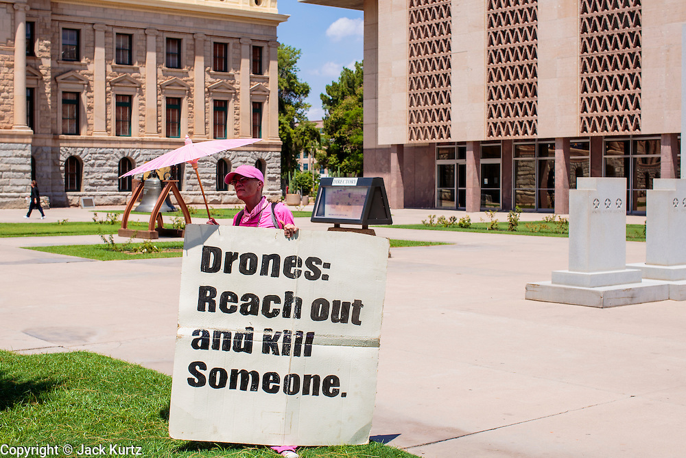 """31 JULY 2012 - PHOENIX, AZ:  LIZ HOURICAN, member of Code Pink stands in front of the Arizona State Capitol in Phoenix waiting for Medea Benjamin, the founder of Code Pink, Tuesday. Benjamin is a political activist, best known for co-founding Code Pink and, along with her husband, activist and author Kevin Danaher, the fair trade advocacy group Global Exchange. She was also a Green Party candidate in 2000 for the United States Senate. She appeared in Phoenix to promote her new book, """"Drone Warfare: Killing by Remote Control."""" She, and other members of Code Pink, presented a letter to Arizona Gov. Jan Brewer protesting Brewer's request to use the state's airspace to train drone pilots.  PHOTO BY JACK KURTZ"""