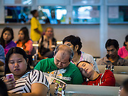 04 JANUARY 2015 - BANGKOK, THAILAND: Passengers nap while they wait to board their bus at the Mo Chit Bus Station. Mo Chit, also called the Northern Bus Station, is the largest bus station in Thailand. Buses from Mo Chit go to most places in Thailand, including the Isan region, the northern cities of Chiang Mai and Chiang Rai, and the Burmese border. Millions of Thais hit the road Sunday returning to Bangkok after the long weekend New Year holiday. Train stations and trains were packed and the state owned bus company scheduled thousands of extra buses to handle the demand.    PHOTO BY JACK KURTZ