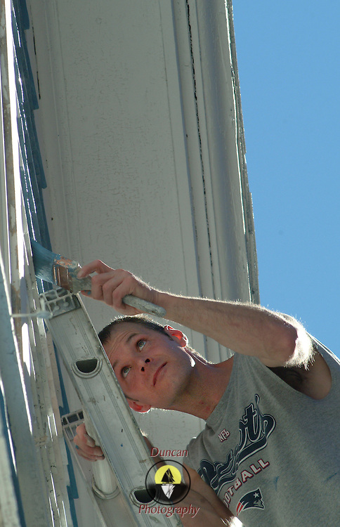 October 22, 2007 -- BATH, Maine. Cory McNeill (originally of Bath), of Portland, paints a home on Middle Street in Bath on Monday afternoon. Warm South winds drove inland temperatures into the low 80s inland and into the high 70s along the coast. Photo by Roger S. Duncan.