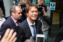 © Licensed to London News Pictures. 18/07/2018. London, UK. SIR CLIFF RICHARD (centre) arrives at the Rolls Building of the High Court in London where judges will deliver their decision on his claim for damages against the BBC for loss of earnings. The 77-year-old singer is suing the corporation after his home in Sunningdale, Berkshire was raided following allegations of sexual assault made to Metropolitan Police. Photo credit: Rob Pinney/LNP