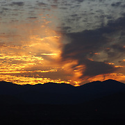 Medford in Southern Oregon is located in the Rogue Valley which has mountains on the west and east sides of the valley.  Sunset with scattered clouds.