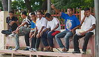 Young men sit on a bench in Dili, Timor-Leste (East Timor).