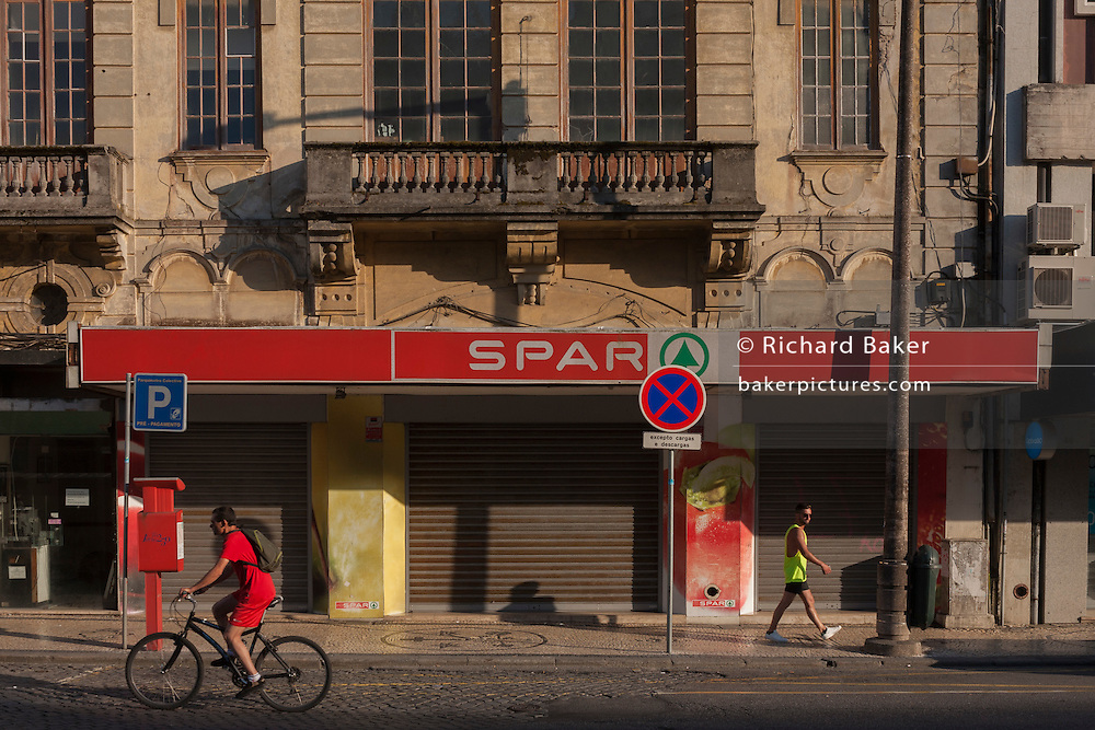 Two young men, one a cyclist and the other in a sports vest, pass each other on the street, outside the premises of a Spar supermarket, on 17th July, at Avenida Dr. Lourenco Peixnho, in Aveiro, Portugal. (Photo by Richard Baker / In Pictures via Getty Images)