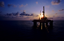 Stock photo of the silhouette of a semi submersible offshore drilling rig on the ocean