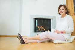 Portrait of senior woman sitting in front of fireplace, smiling