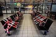 Afgeplakte bankjes in de wachtruimte van de aankomsthal op Schiphol Airport