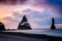 VIK, ICELAND - CIRCA MARCH 2015: Black sand beach of Reynisfjara, near Vik, and basalt sea stacks in southern Iceland at sunrise.