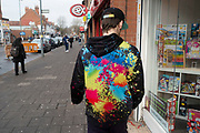 Young man wearing a multicoloured paint splat urban wear top on Kings Heaht High Street in Birmingham, United Kingdom.