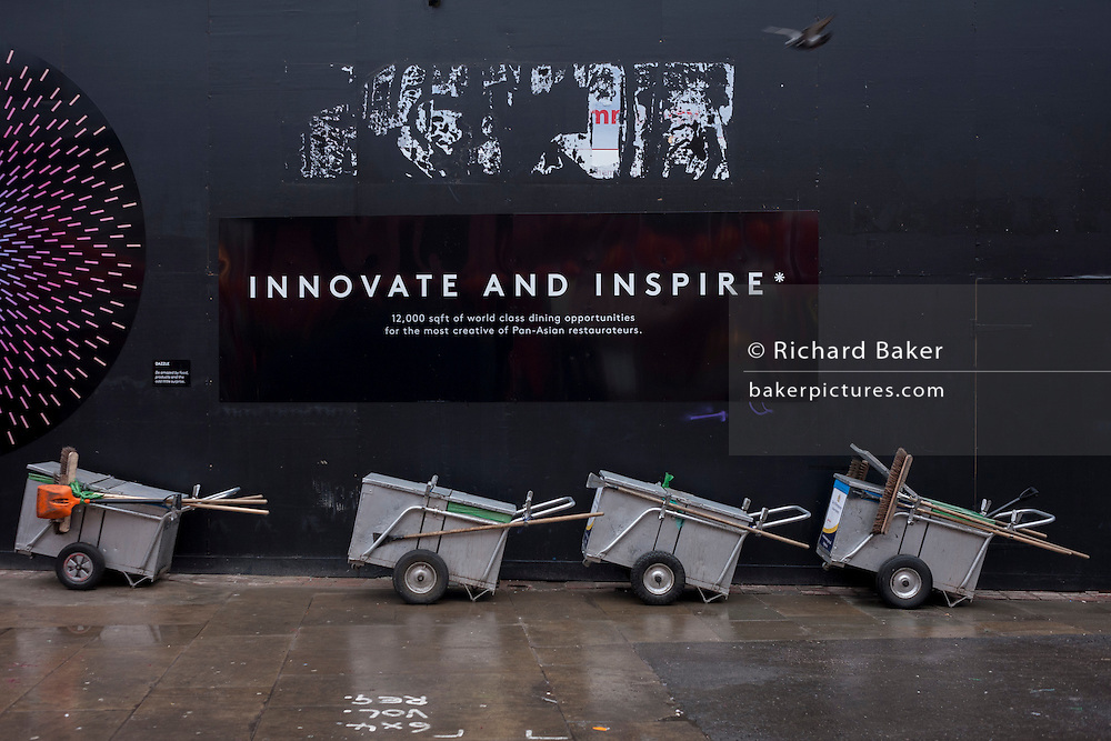 A dystopian landscape of Westminster council sweepers' barrows and an inspirational corporate slogan on a construction hoarding, on 31st January 2017, in Chinatown, London, England.