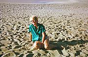 Expatriate tourist woman sitting on sandy beach, island of Tobago, 1963