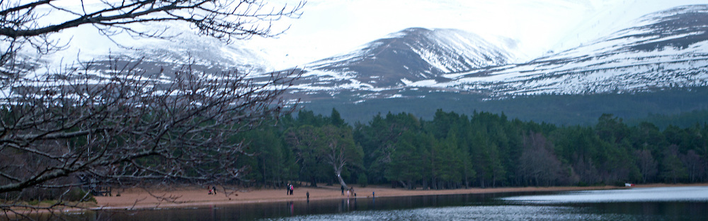 Beach at Loch Morlich with snow capped Cairngorms